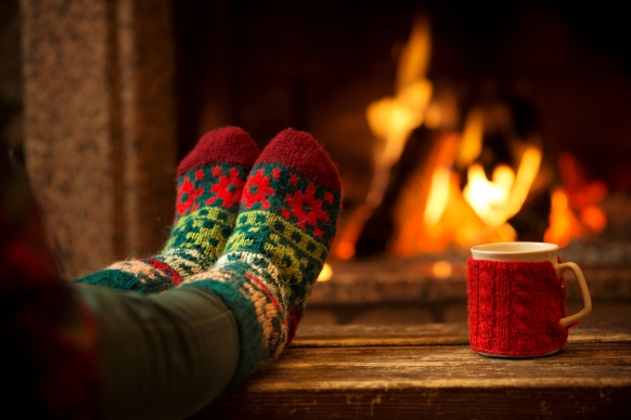 Feet in comfy woollen socks and a cup on table with fireplace in the background