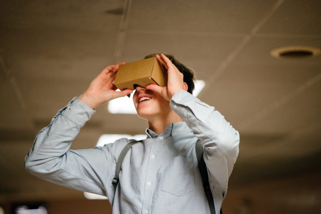 Young man looking through paper VR glasses